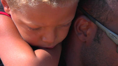 A small boy leans over his father's shoulder Stock Video Footage