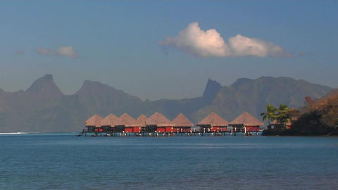 Tahitian huts on the water with mountain crest line in... Stock Video Footage