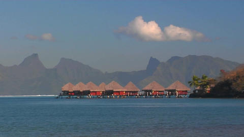 Tahitian huts on the water with mountain crest line in the distance Footage
