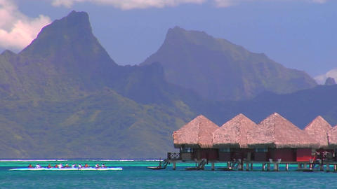 Tahitian huts on the water with mountain peaks in the background as rowers pass by Footage