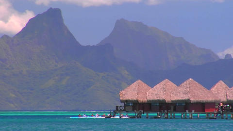 Tahitian huts on the water with mountain peaks in the... Stock Video Footage