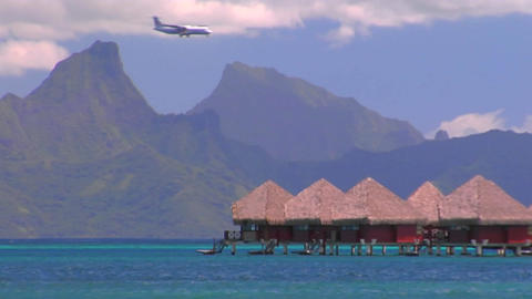Tahitian huts on the water with sharp mountain peaks in the background and an airplane passes throug Footage