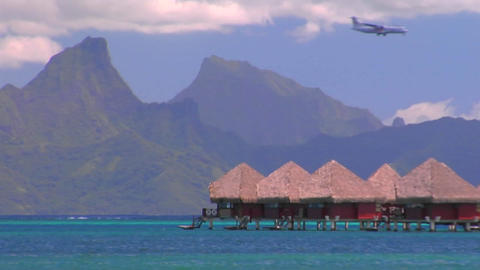 Tahitian huts on the water with sharp mountain peaks in... Stock Video Footage