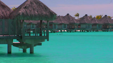 Tahitian huts rest over turquoise water Footage