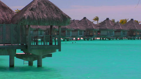Tahitian huts rest over turquoise water Stock Video Footage