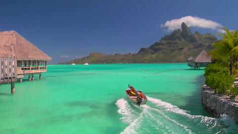 Tahitian huts rest over turquoise water as small boat passes through and waves Footage