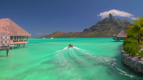 Tahitian huts rest over turquoise water as small boat... Stock Video Footage