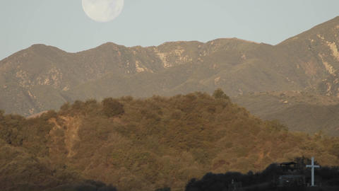 Time lapse of full moon setting behind mountains and sunrise on a cross in Oak View, California Footage