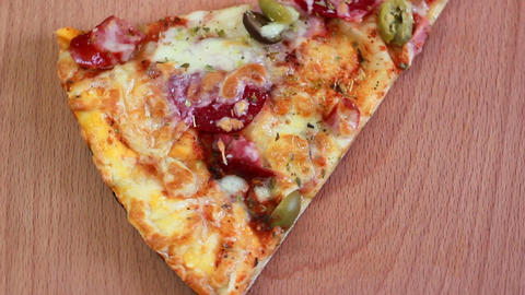 Closeup piece of pizza rotation on wooden plate Live Action