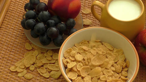 Corn flakes and milk falling in a bowl. Healthy food Footage