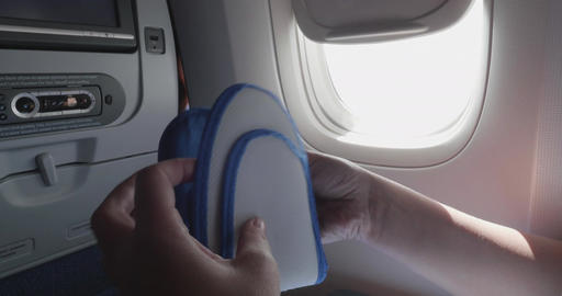 Shot of woman opening disposable slippers in airplane Live Action