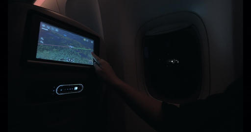 Woman looking at plane route on seat monitor Live Action