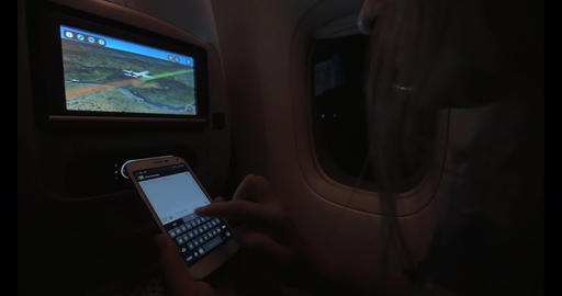 Woman typing SMS during night flight Live Action