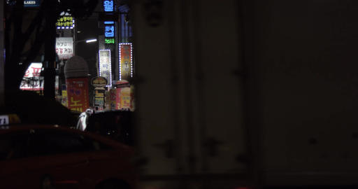 Street with illuminated banners, people and cars in night Seoul, South Korea Footage