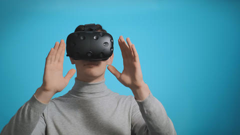 man plays video game using modern virtual reality headset Live Action