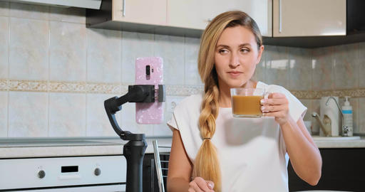 blogger looks in smartphone camera and drinks milk coffee Live Action