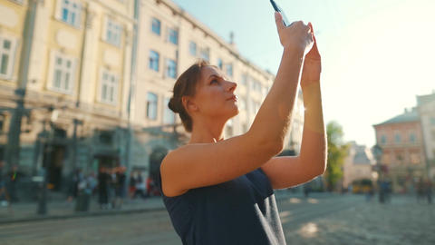 Woman stands on an old street and takes a photo or video on a smartphone at Live Action