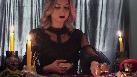 Young fortune teller at the table by candlelight reads the future on the cards Live Action