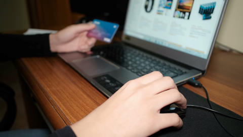 Young woman browsing ecommerce store on a laptop for web shopping,credit card Live Action