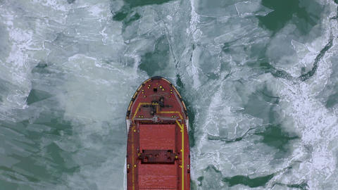 Aerial above epic huge steel ship breaks ice by bow of ship and floats in large Live Action