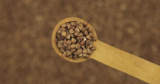 Buckwheat grains in a spoon. Refocusing from a spoonful of grain to a pile of Live Action