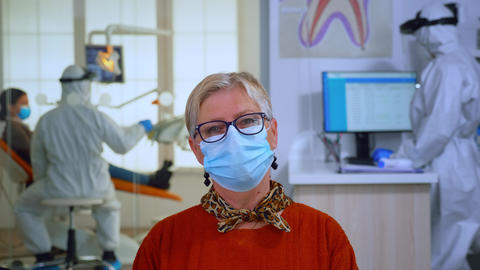 Portrait of retired patient with mask in dental office looking on camera Live Action