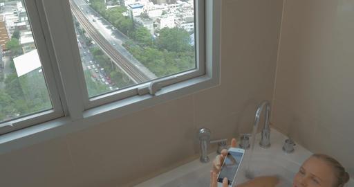 Woman in bath taking selfie with smart phone Footage