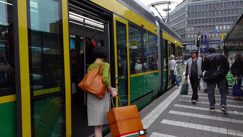 Asian woman come inside modern tram, doors closing and vehicle depart from stop Footage
