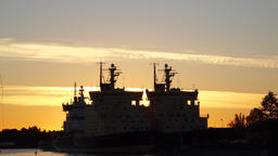 Two twin Icebreaker ship black silhouettes against sunrise sky, early morning Footage
