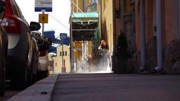 Cleaner man use pressure washer on sidewalk, slow motion candid shot Footage