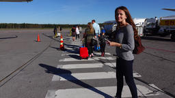 Woman come to airliner, walk with people at apron area, look back to airport Live Action
