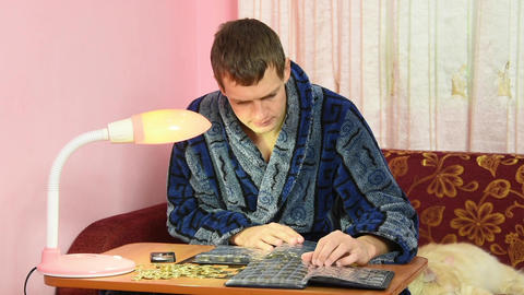 A young man in a dressing gown watching his collection of coins in albums Live Action