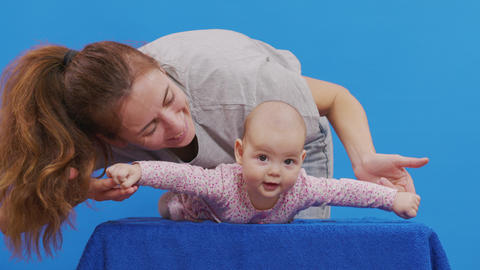 Mom plays with her newborn daughter. Isolated on blue background Live Action