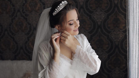 Bride in boudoir dress puts on earrings. Wedding morning preparations. Woman in Live Action