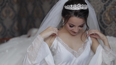 Bride in white boudoir dress, veil and in a silk robe. Wedding morning Live Action