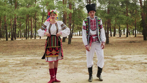 Young woman and man in traditional costumes are dancing Ukrainian national dance Live Action