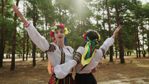 Two beautiful women in traditional costumes are dancing Ukrainian national Live Action