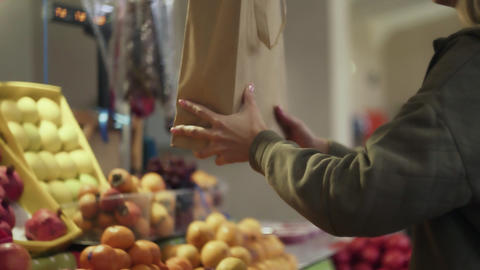 Young woman gives a paper bag to seller at market Live Action