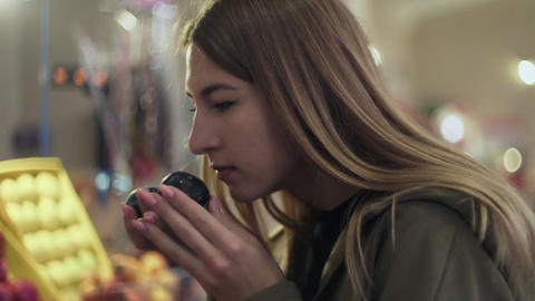 Young woman sniffs and chooses plums on store shelves at the market Live Action
