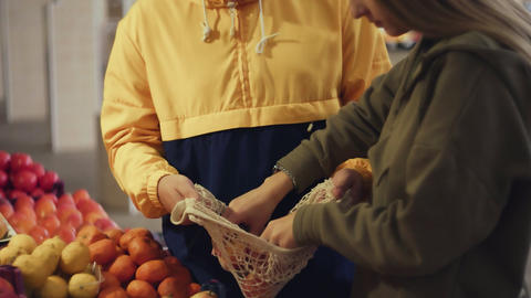 Young couple choose peaches and puts them into string bag at the market Live Action