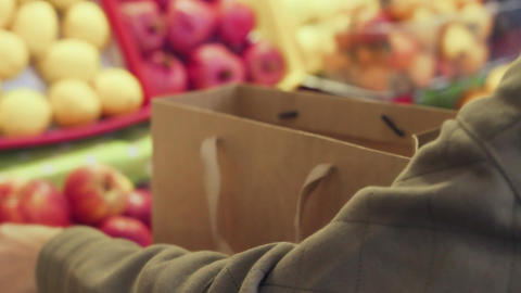 Close up of woman puts red apples into a paper bag at market Live Action