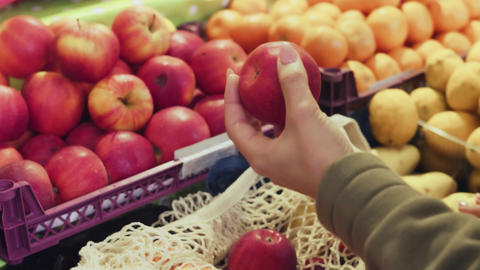 Close up of woman puts red apples into string bag at market Live Action