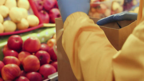Close up of man puts red apples into a paper bag at market Live Action