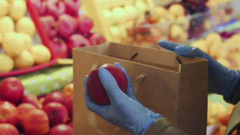Close up of woman in blue gloves puts red apples into a paper bag at market Live Action