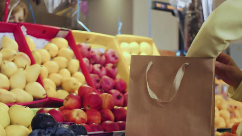 Back view of woman in yellow coat puts red apples into a paper bag at market Live Action