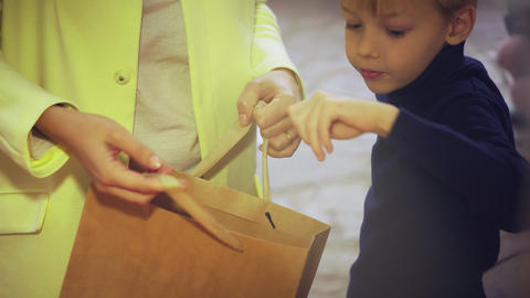 Little boy with his mother at the market. Boy puts mandarins into a paper bag Live Action