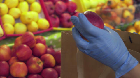 Close up of woman in blue gloves puts red apples into string bag at market Live Action