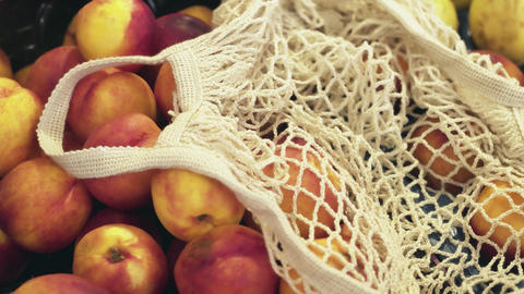 Close up of woman in back sweater puts fresh peaches into string bag at market Live Action