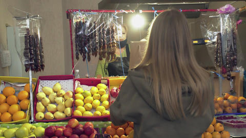 Back view of young woman gives a paper bag to seller at market Live Action