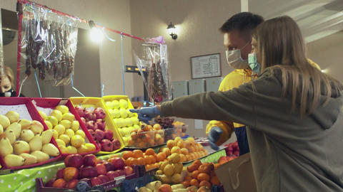 Young couple protective masks and gloves chooses fruits at the market Live Action